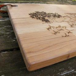 """planche à découper en chêne gravée d' un motif """" Du soleil et du bon vin""""."""