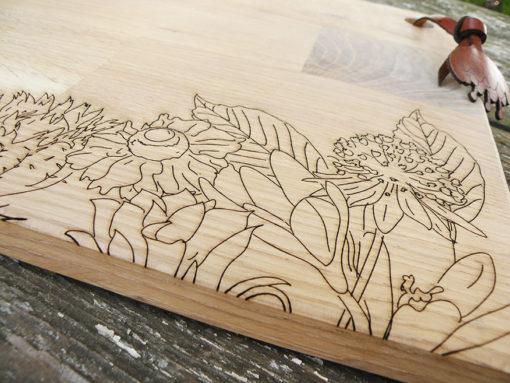 Planche à découper en chêne gravée à la découpe laser, avec un motif floral.