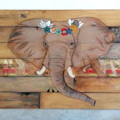 tableau gravé, peint à la maint et collage qui représente un portrait d' éléphant arborant une couronne de fleur .